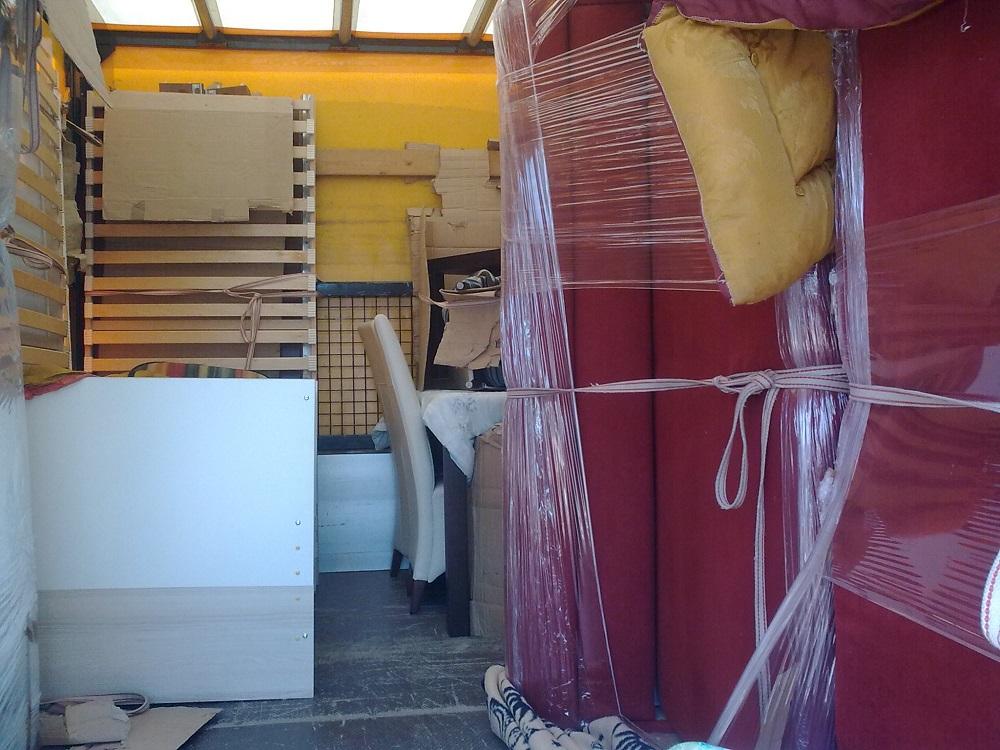 Rögzített, csomagolt bútorok a teherautó rakterében.